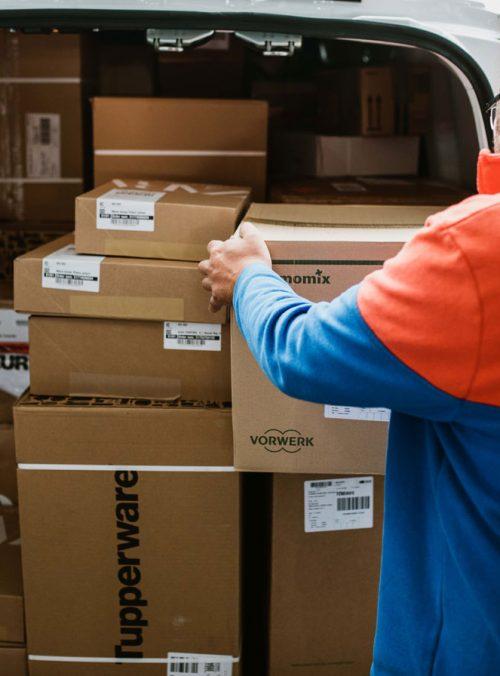 Trabajador SEUR cargando cajas en coche