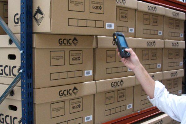 Empleado con aparato leyendo código de barras de una caja