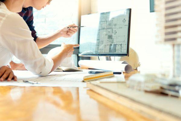 Trabajadores hablando mientras observan una pantalla de ordenador