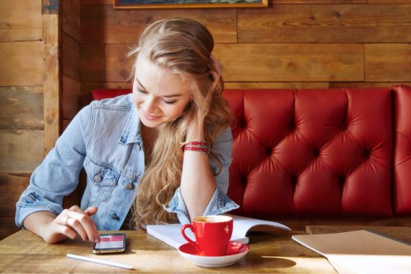 chica en cafetería mirando el móvil